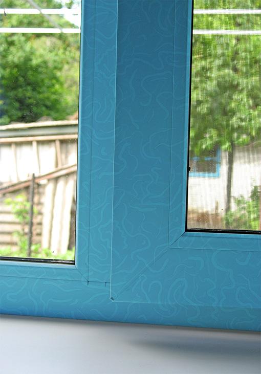 Покрашенное в синий узор пластиковое окно
