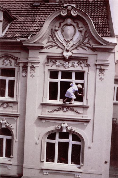 Бабулька моет окно снаружи дома на втором этаже