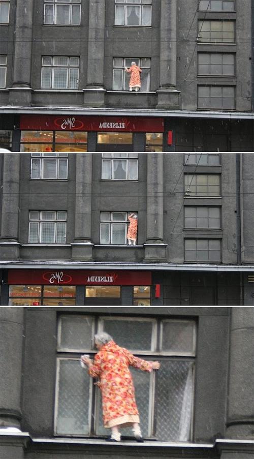 Бабка моет окно зимой снаружи дома, стоя на карнизе