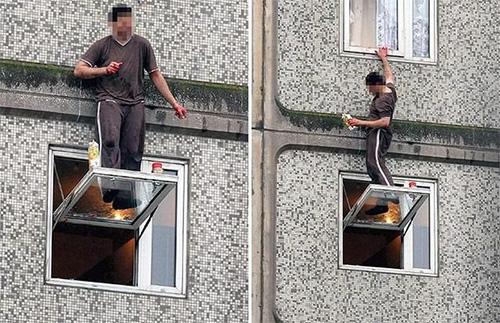 Мужик стоя на стекле открытого окна моет другое окно