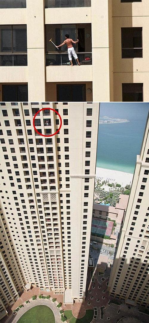 Мужик на стометровой высоте моет окно снаружи небоскреба